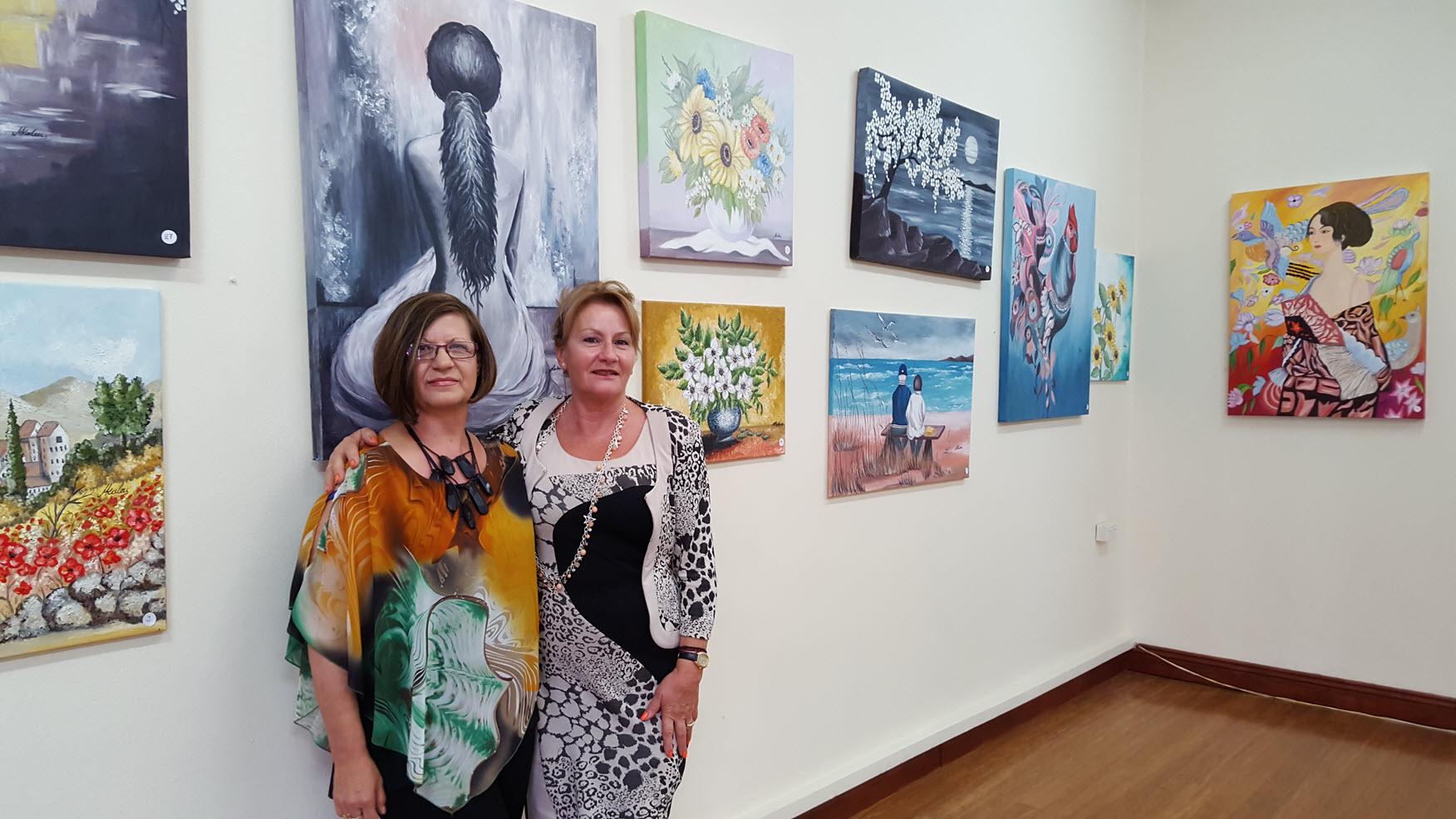 Artist Mary Kalaitzis with Toula Mavroudis among the paintings